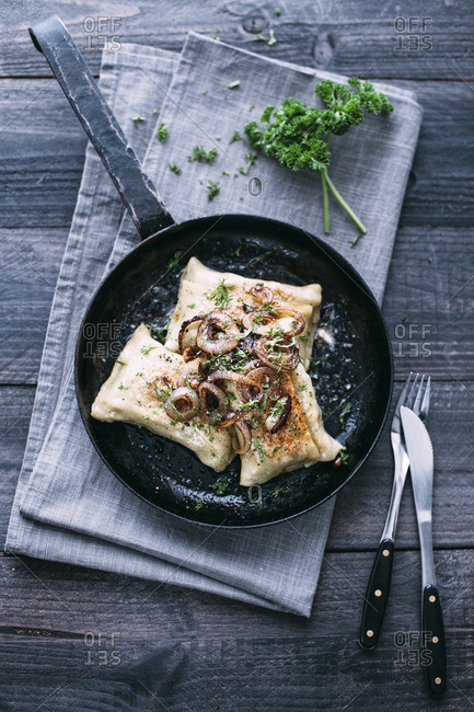 Vegetarian Swabian pockets with roasted onions in frying pan