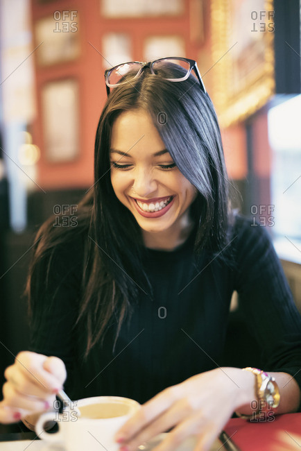 Portrait of laughing young woman in a coffee shop