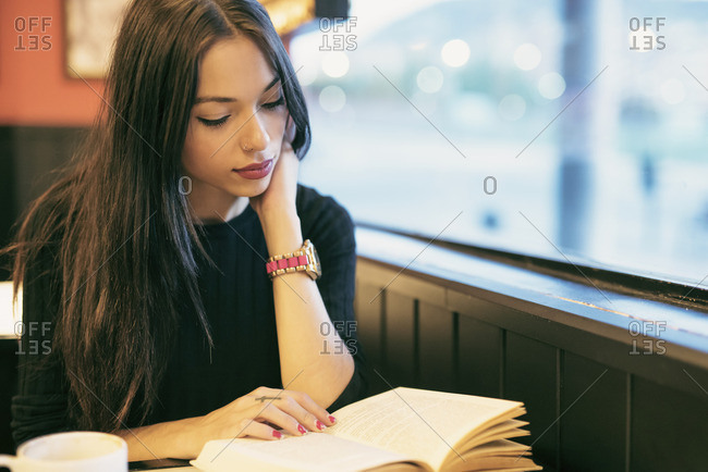 Young woman sitting in a coffee shop reading a book