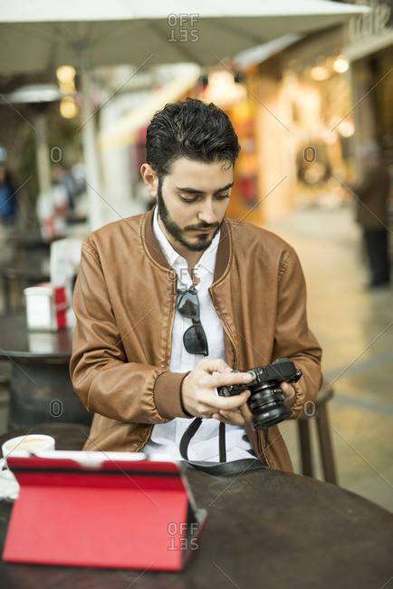 Young man looking at camera at outdoor cafe