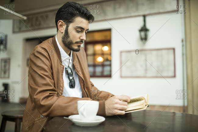 Young man reading book at outdoor cafe