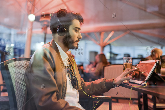 Young man with headphones using tablet at outdoor bar