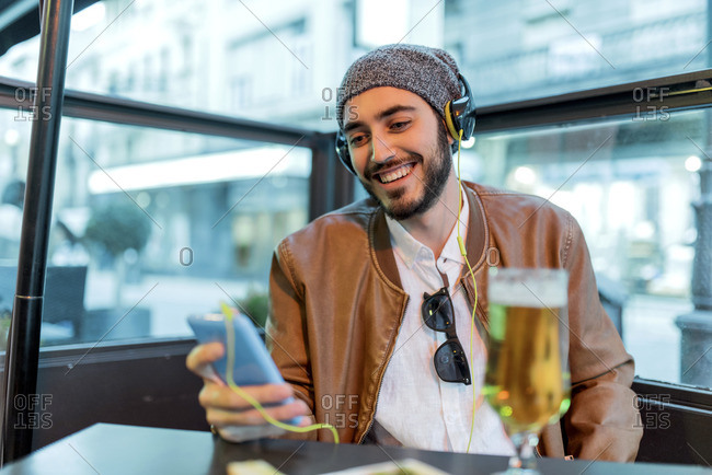 Smiling man with headphones and cell phone at outdoor bar