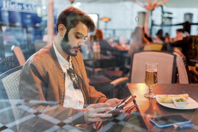 Young man using tablet at outdoor bar