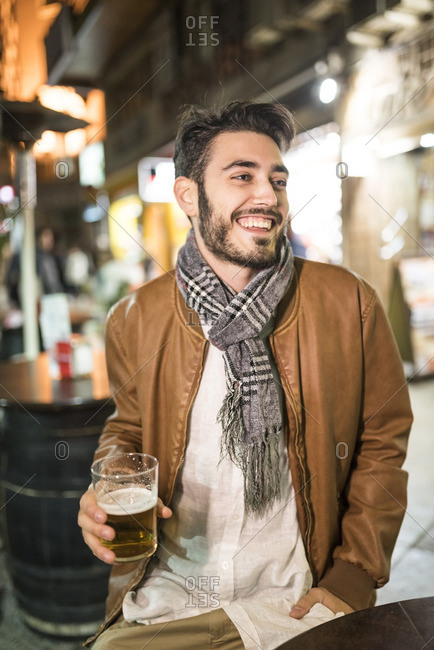 Happy man with beer at outdoor bar