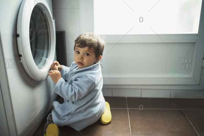 Baby boy crouching in front of washing machine