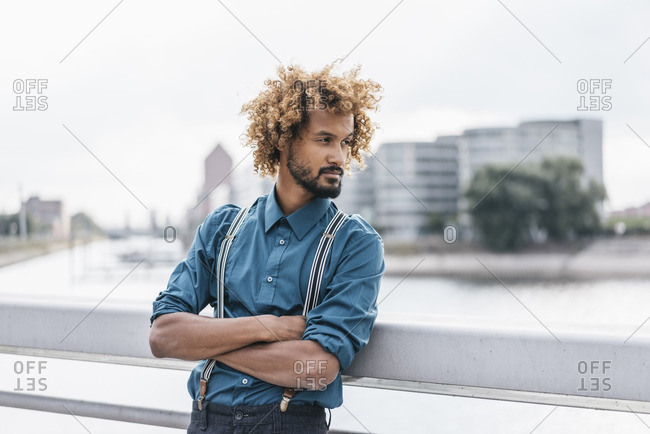 Young man leaning on railing with arms crossed