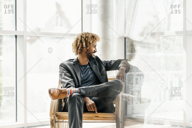 Young businessman sitting in wooden rocking chair