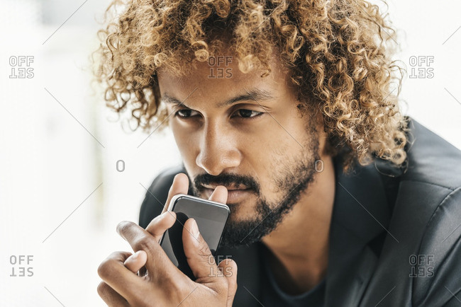 Young businessman with smart phone looking thoughtful