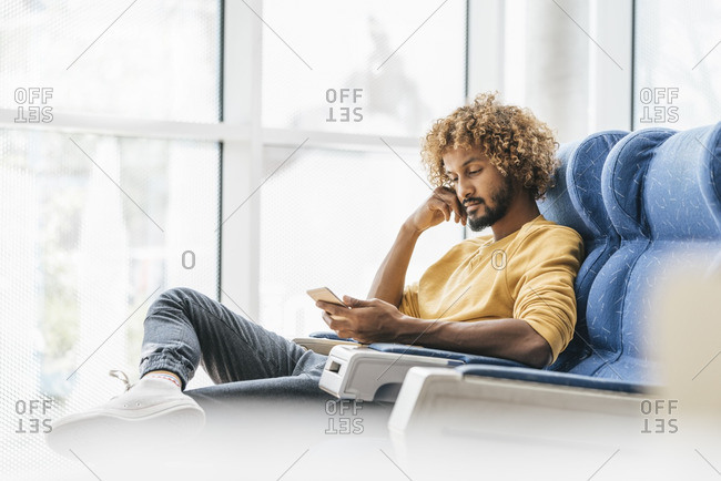 Young man sitting in chair- reading messages