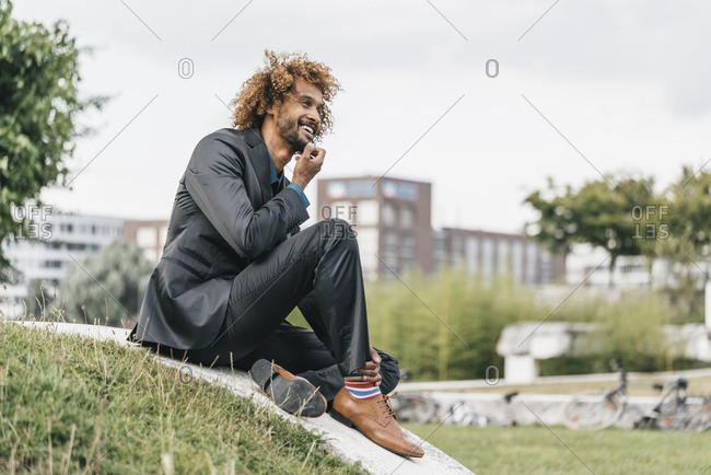 Young businessman sitting on wall