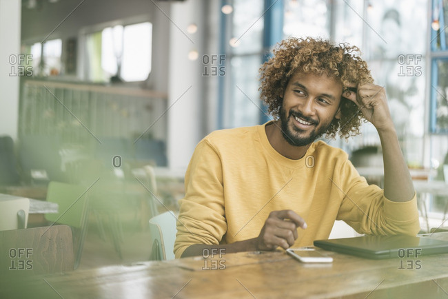 Young man sitting at table- working with laptop
