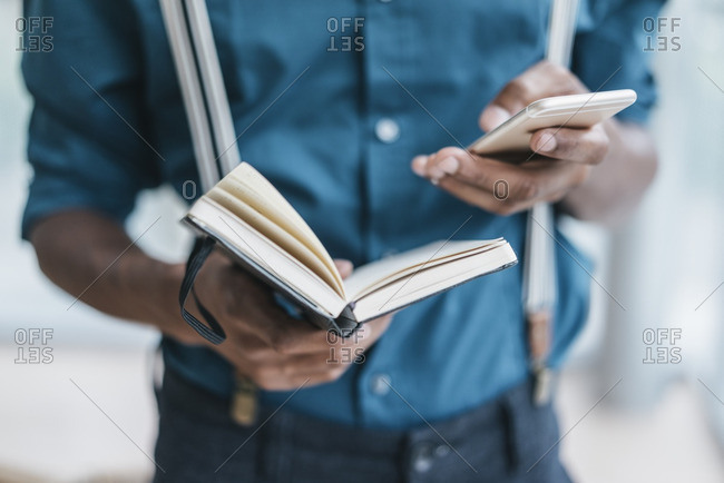 Young man using smart phone- holding note book