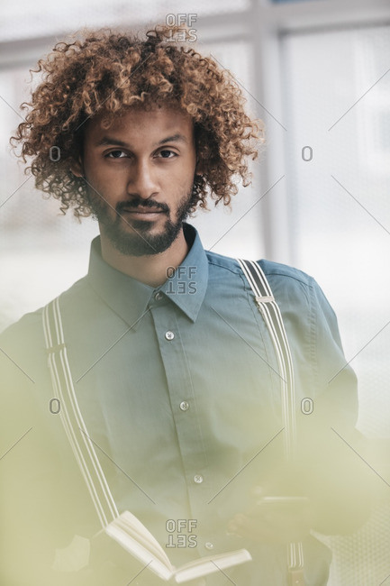 Portrait of y young man holding note book and mobile phone