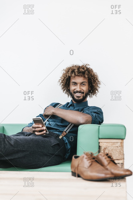 Young man using smart phone- laughing