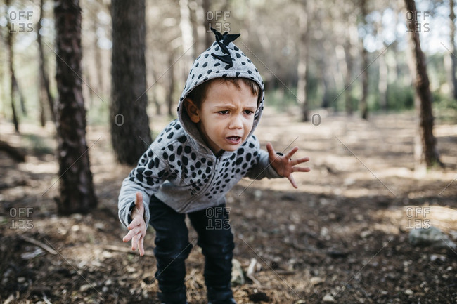 Portrait of little boy wearing hooded jacket playing monster in the woods