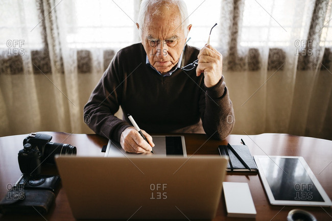 Senior photographer working with laptop