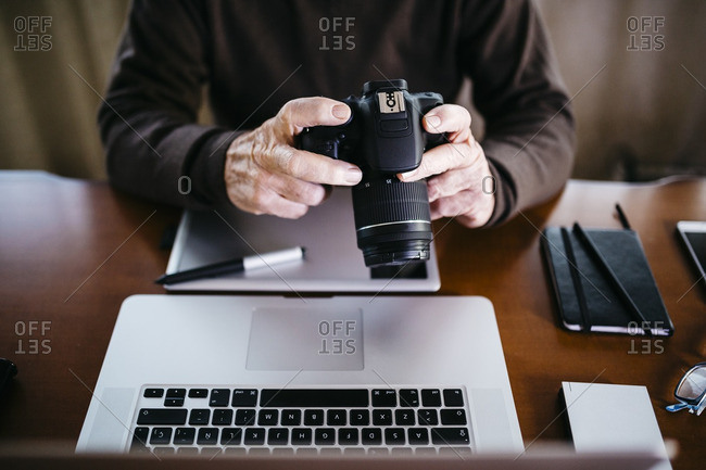 Senior photographer with laptop and digital camera at home- partial view