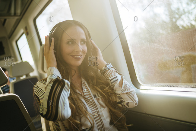 Woman on a train listening to music with headphones
