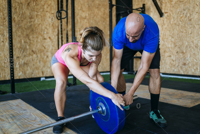 Man and woman preparing barbell in gym