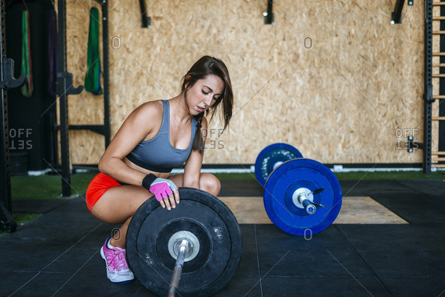 Woman preparing barbell in gym