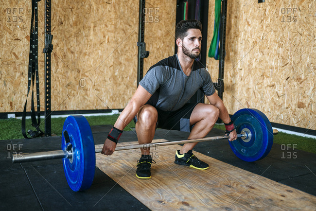 Man ready to lift barbell in gym