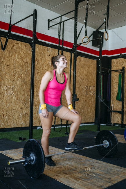 Woman resting on a barbell in gym