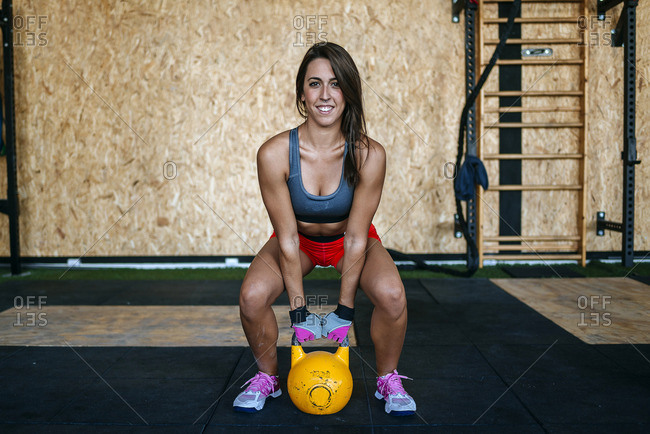 Woman preparing to lift kettlebell in gym