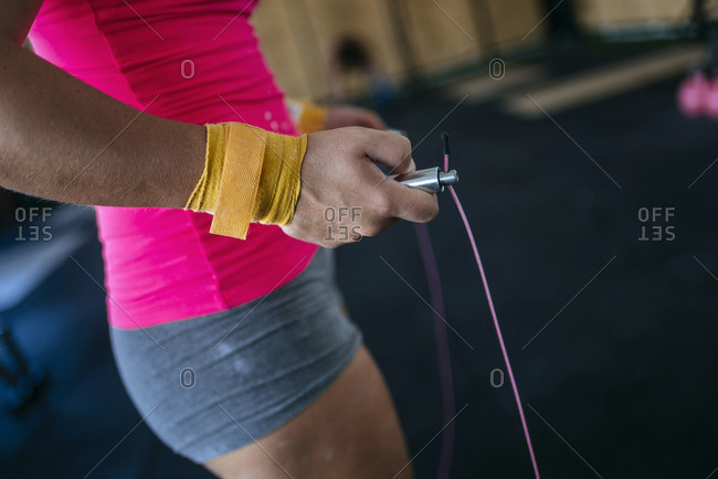 Close-up of woman holding skipping rope in gym