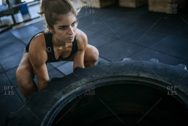 Woman exercising with a tractor tire in gym
