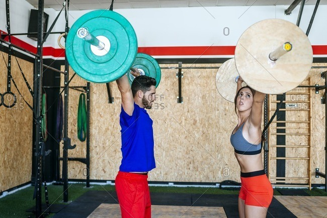 Man and woman lifting barbells in gym