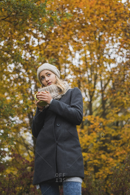 Young woman with hot beverage in autumn forest