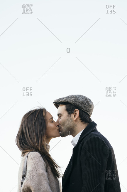 Couple kissing in front of sky