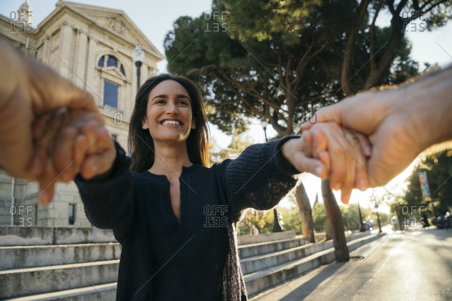 Spain- Barcelona- portrait of happy woman holding hands with her husband
