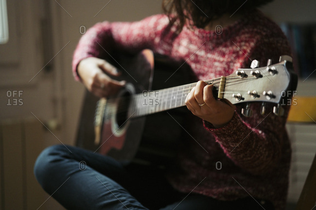 Young woman playing guitar at home