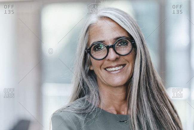 Portrait of smiling woman with long grey hair