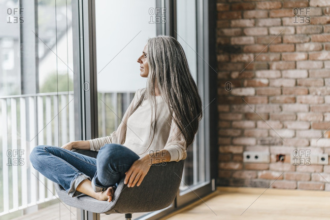 Woman with long grey hair sitting on chair at the window