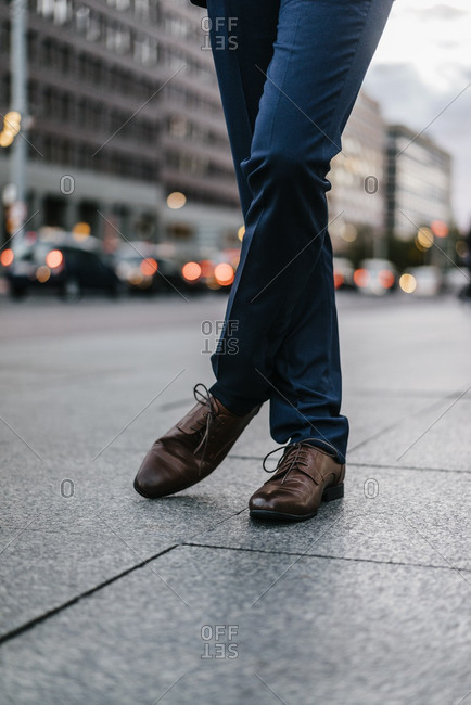 Businessman standing on pavement- partial view