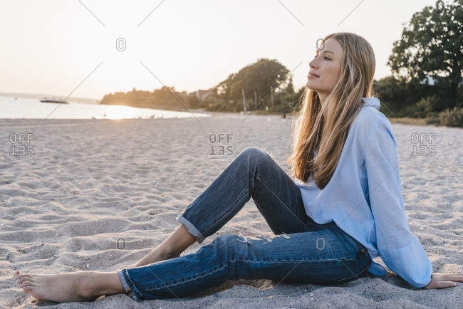 Young woman relaxing on the beach in the evening