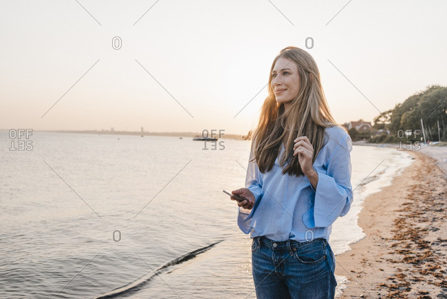 Smiling young woman with smartphone standing on the beach