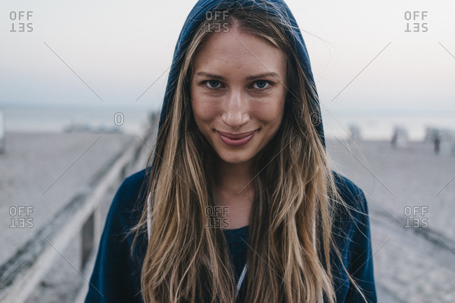 Portrait of smiling young woman wearing hooded jacket standing on jetty