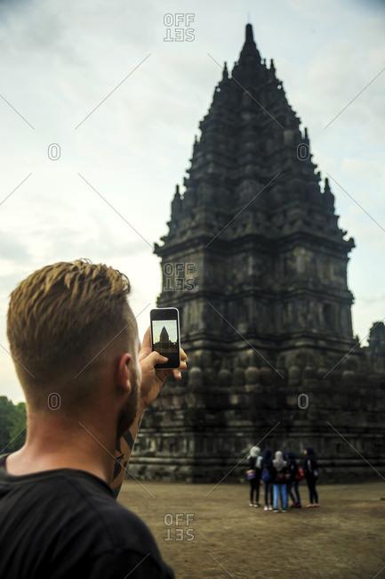 Indonesia- Java- Tourist photographing Prambanan temple