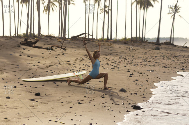 Indonesia- Bali- woman with surfboard stretching on the beach