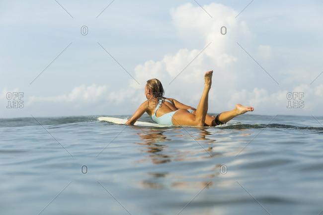 Indonesia- Bali- woman floating on bodyboard in the sea