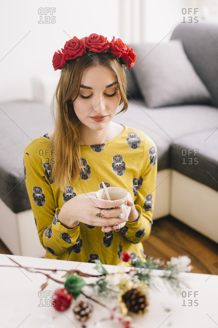 Young woman wearing floral wreath relaxing with cup of coffee at home at Christmas time