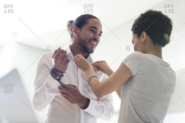 Woman adjusting man's white shirt