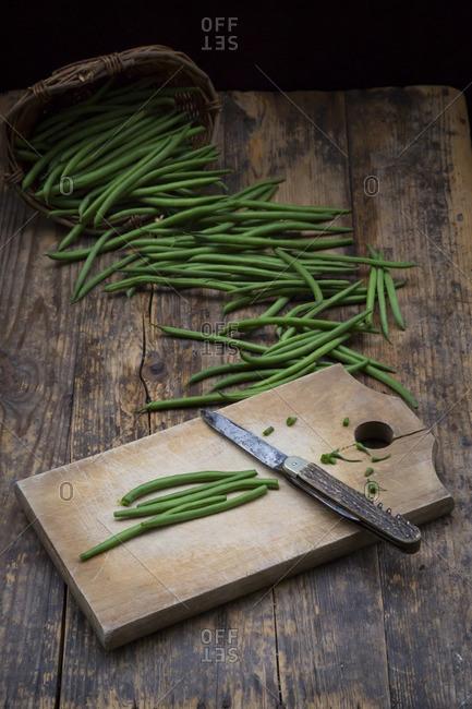 Wickerbasket- green beans- wooden board and pocket knife on dark wood