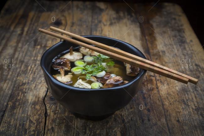 Bowl of miso soup with organic tofu- shitake mushrooms- leek and parsley on dark wood