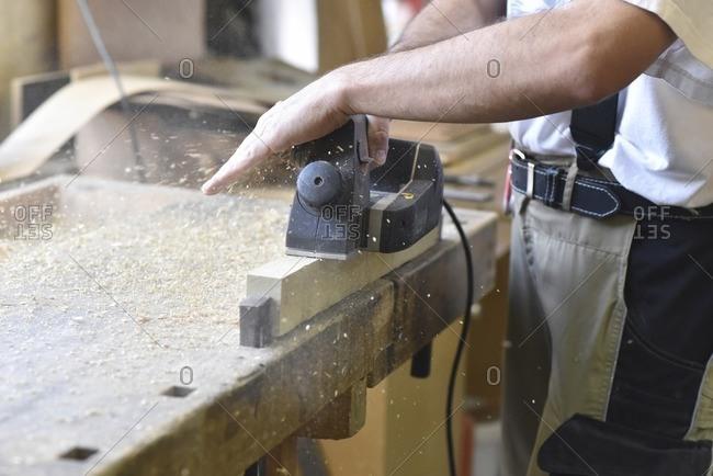 Carpenter working with plane in workshop