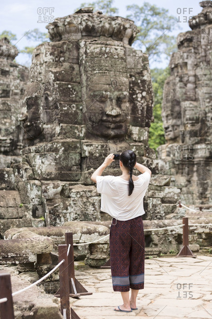 Cambodia- Siem Reap- Angkor Thom- back view of tourist taking pictures of Bayon temple